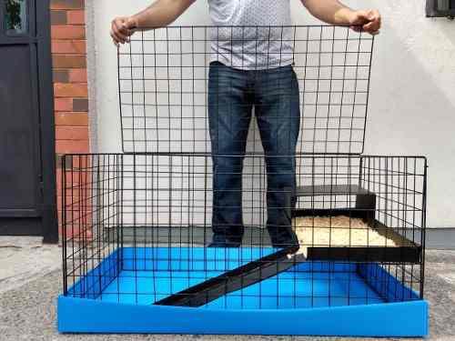 Jaula nueva cuyos 1/2 piso azul negro con heno y aserrín
