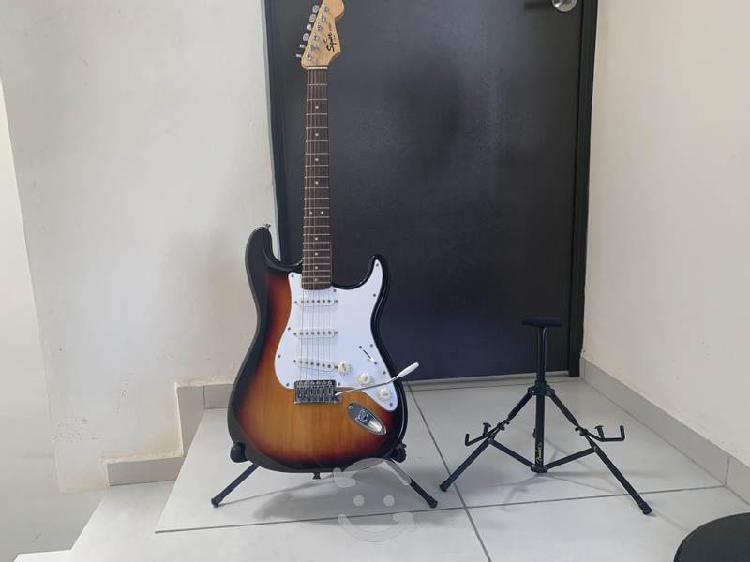 Guitarra eléctrica con amplificador y soportes